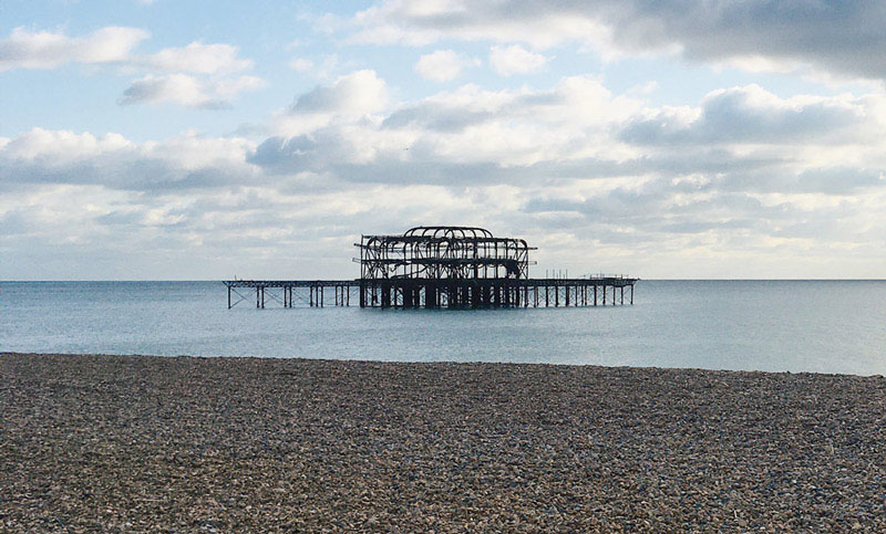 Brighton old pier on a partly cloudy day.
